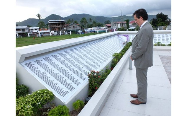 Solemn moment at the memorial at Tacloban Astrodome, where the names of the typhoon victims are engraved